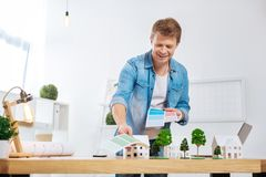 Handsome man looking happy while holding color palettes and changing them. Suitable colors. Attentive responsible young engineer having a productive day at work Royalty Free Stock Image