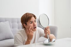 Handsome man looking at himself in mirror. Squeezing pimple. Handsome man looking at himself in mirror. Squeezing pimple stock photos