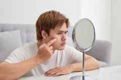 Handsome man looking at himself in mirror. Squeezing pimple. royalty free stock images