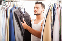Handsome man looking at his closet Stock Images