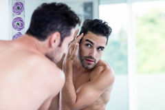 Handsome man looking at his hair royalty free stock images