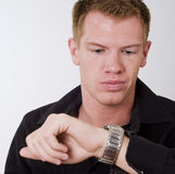 Handsome man looking at his watch royalty free stock photos