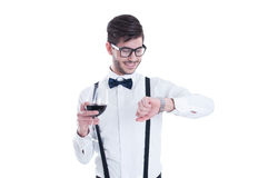 Handsome man is looking at his watch smiling. Holding a glass of Stock Image