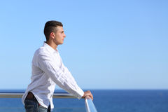 Handsome man looking at the horizon. With the sea and a blue sky in the background Stock Images