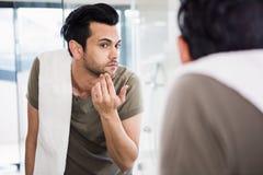 Handsome man looking in mirror stock photos