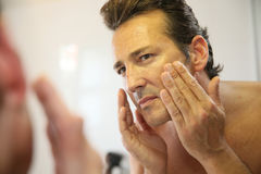 Handsome man looking at he mirror washing his face Royalty Free Stock Photos