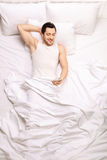 Handsome man looking at mobile phone while lying in bed Royalty Free Stock Photography