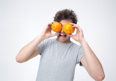 Handsome man looking through oranges Stock Image