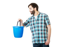 Handsome man looking into plastic bucket. Royalty Free Stock Photo