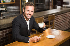 Handsome man looking at smartphone and having a coffee Stock Image