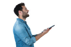 Handsome man looking up while holding a digital tablet Royalty Free Stock Photo