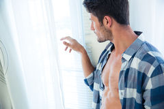 Handsome man looking in window Royalty Free Stock Image