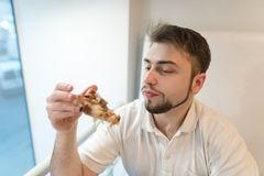 A handsome man looks closely at a piece of pizza in his hands. Student eats pizza for lunch. Royalty Free Stock Photography