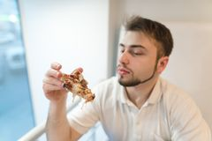 A handsome man looks closely at a piece of pizza in his hands. Student eats pizza for lunch. Stock Image