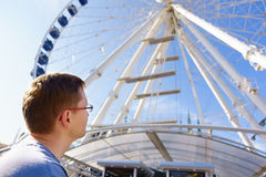 Handsome man looks at ferris wheel against a blue sky Royalty Free Stock Image