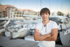 Handsome man by luxury yacht background on the beach at sunset. Royalty Free Stock Image