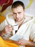 Handsome man lying in bed Stock Images