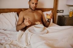Handsome man lying on bed, happy smile drink orange juce in the morning. Attractive guy smiling in bedroom at home,. Young male model royalty free stock photography