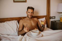 Handsome man lying on bed, happy smile drink orange juce in the morning. Attractive guy smiling in bedroom at home,. Young male model royalty free stock images