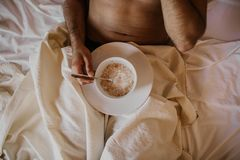 Handsome man lying on bed with healthy breakfast in the morning. Attractive guy smiling in bedroom at home, young. Male model royalty free stock photo