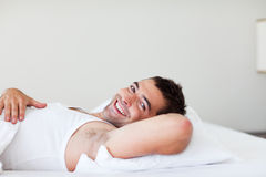 Handsome man lying in bed smiling Royalty Free Stock Photo