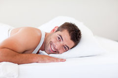 Handsome man lying in bed smiling Stock Photography