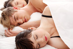Handsome man lying in bed with two girls Royalty Free Stock Images