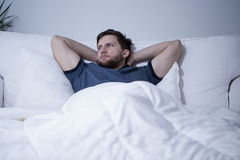 Handsome man lying in bed Royalty Free Stock Image