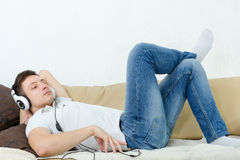 Handsome man lying on couch with headset listening to music royalty free stock photos