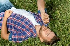 Handsome man lying on the grass Stock Photography