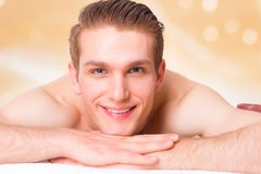 Handsome man lying on the massage desks. Royalty Free Stock Photography