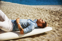 Handsome man lying on surfboard at beach Royalty Free Stock Image