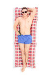 Handsome man lying on a swimming mattress Royalty Free Stock Photo