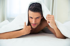 Handsome man lying under blanket in the bed Stock Photos