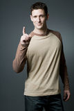 Handsome man makes a pointing gesture. Stock Photo