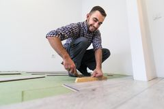 Repair man making the laminate flooring installation. Handsome Man making the laminate flooring installation Royalty Free Stock Photos