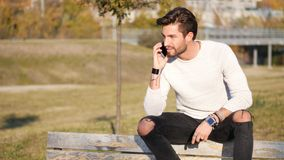 Young man making phone call outdoor in city. Handsome man making phone call outdoor in urban environment on with cell phone royalty free stock image