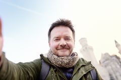 Handsome milddle age man making a self portrait selfie with famous royal castle Neuschwanstein on background. Handsome man making a self portrait selfie with stock photography