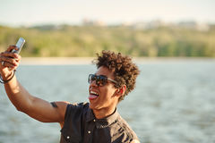 Handsome man making selfie and grimacing with opened mouth Royalty Free Stock Images