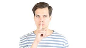 Handsome man making a shushing gesture raising his finger to his lips royalty free stock images