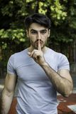 Handsome man making a shushing gesture Royalty Free Stock Images