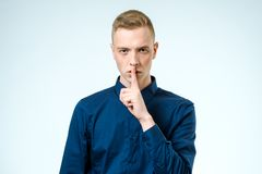 Handsome man making silence gesture. Isolated Stock Photo