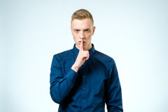 Handsome man making silence gesture Stock Photo