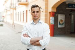 Handsome man manager with a white shirt hairstyle crossed. His arms in the city stock images