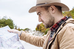 Handsome man with the map in hand standing next to a car in Mont Royalty Free Stock Image