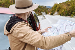 Handsome man with the map in hand standing next to a car in Mont Royalty Free Stock Photo