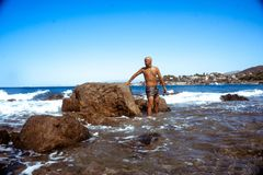 Handsome man on the marine rocky shore royalty free stock images