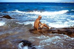 Handsome man on the marine rocky shore royalty free stock image