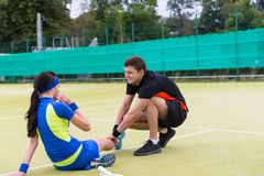 Handsome man massaging woman`s injured leg after  tennis match Stock Images