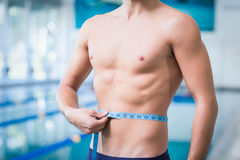 Handsome man measuring his waist. At the pool Stock Images